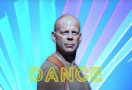 Bruce Willis, bruised and scratched, stares out at the camera in front of a bright blue and purple background