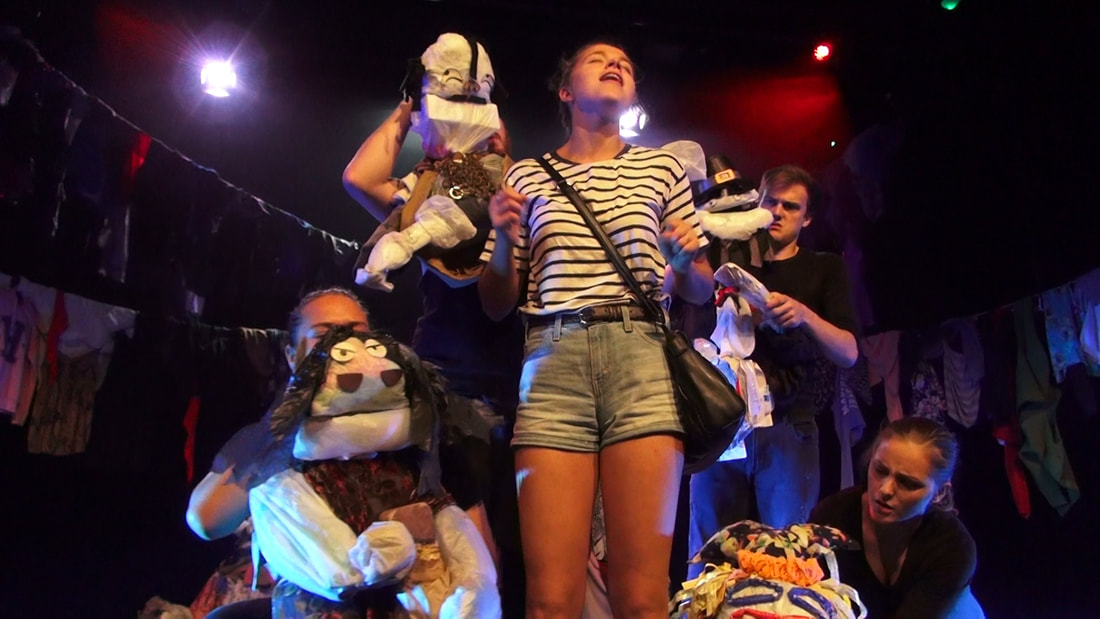 A girl in a striped shirt sings surrounded by four puppets, operated by puppeteers