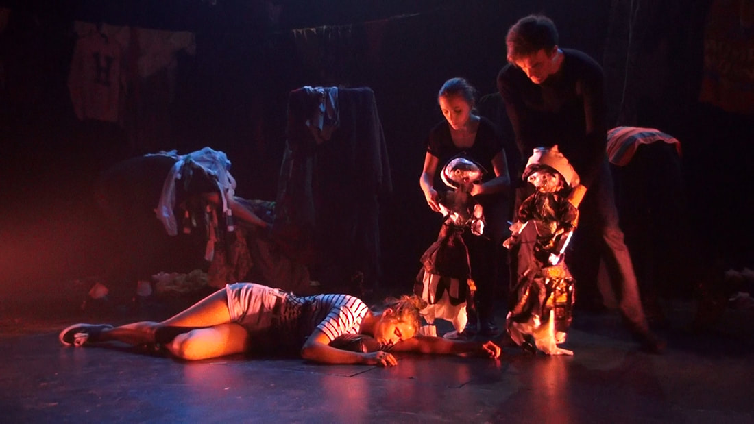 a girl in a striped shirt lies asleep on the floor.  Two puppeteers in black hold half-size puppets of old villagers, who look down at the girl
